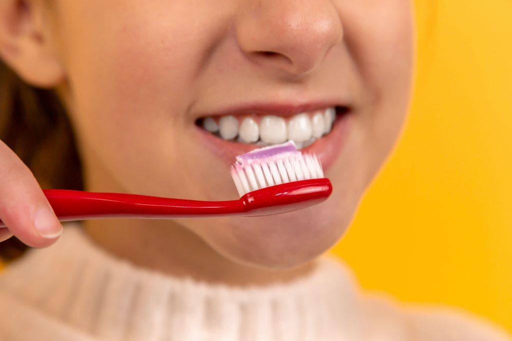 teeth whitening - girl brushing her teeth tooth crown