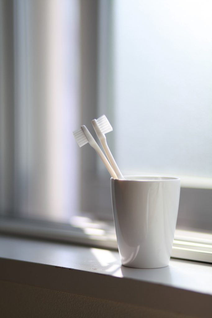 Teeth Whitening Palmview - toothbrushes in cup on window sill